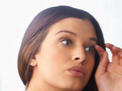یک زن جلوی آیینه در حال بررسی مژه هایش